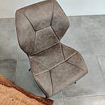Die Sitzfläche und die Lehne sind bequem gepolstert und in geometrischen Mustern abgesteppt.